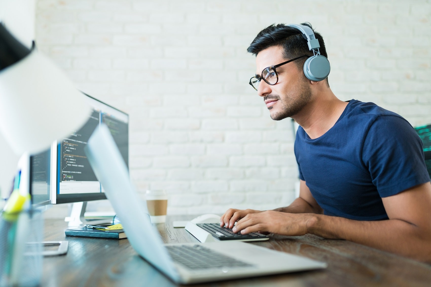 Software developer programming at desk, wearing headphones